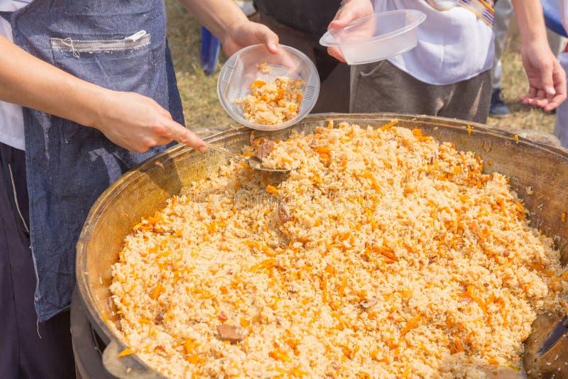 La Russia, samara, luglio 2018: Il cuoco dell'Uzbeco presenta il pilaf cucinato in piatti durante la festa festival Ethno-storico fotografia stock libera da diritti