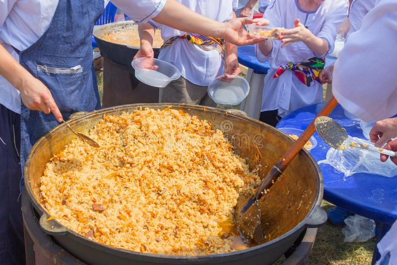 La Russia, samara, luglio 2018: Il cuoco dell'Uzbeco presenta il pilaf cucinato in piatti durante la festa festival Ethno-storico fotografie stock