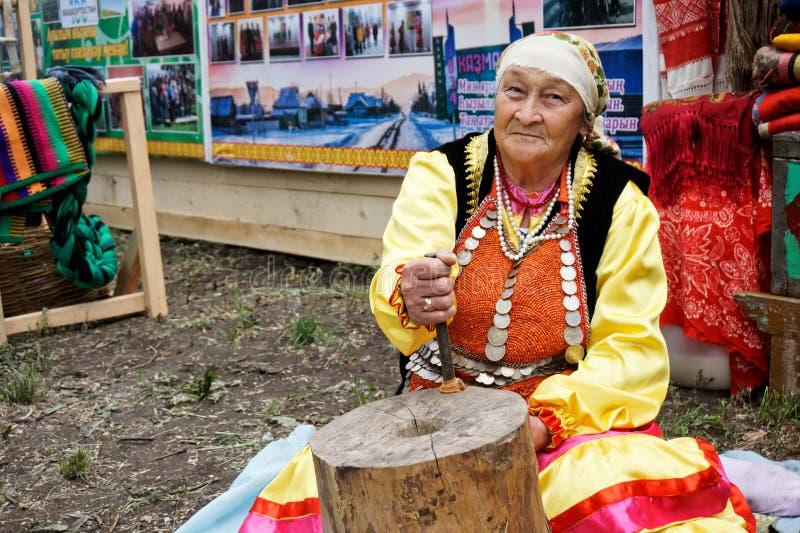 La Russie, Magnitogorsk, - juin, 15, 2019 Une femme agée démontre le travail de la vieille meule manuelle en bois pendant photos stock