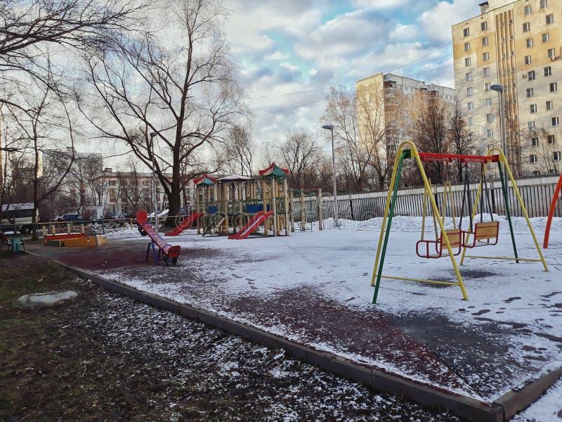 La Russie, Moscou, mars 2019 Terrain de jeu couvert par la neige matin ensoleillé Oscillations et glissières Première source Fond photo stock