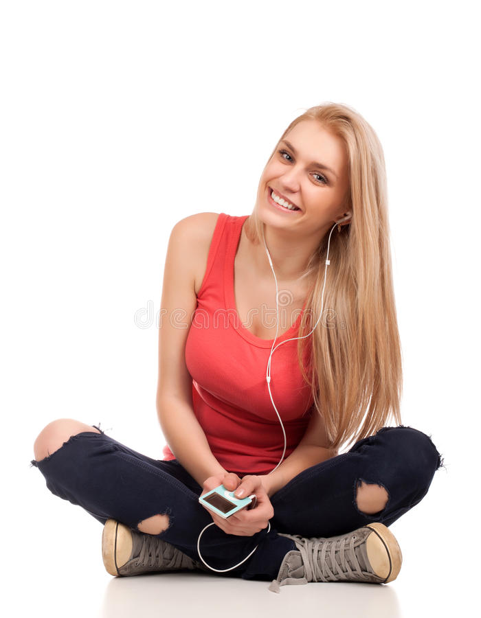 La séance blonde d'adolescente et écoutent musique photographie stock libre de droits