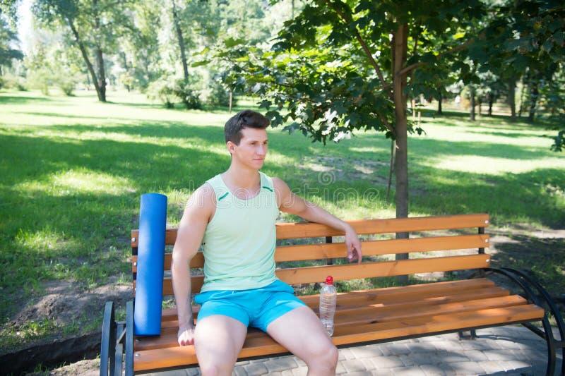 La séance d'entraînement est terminée L'homme avec le tapis de yoga et la bouteille d'eau s'asseyent sur le banc en parc Joignez  images stock