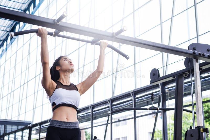 La séance d'entraînement d'exercice de femme de forme physique avec l'exercice-machine tirent vers le haut sur la barre dans le g photos libres de droits