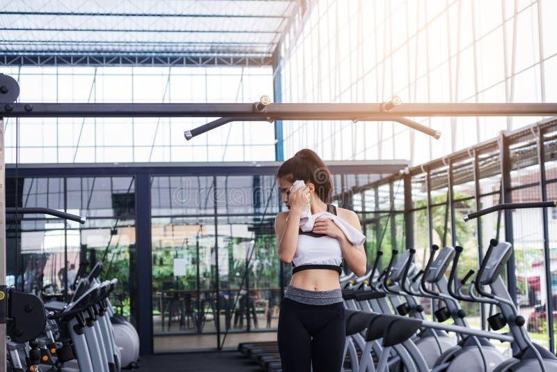 La séance d'entraînement d'exercice de femme de forme physique avec l'exercice-machine tirent vers le haut sur la barre dans le g photos stock