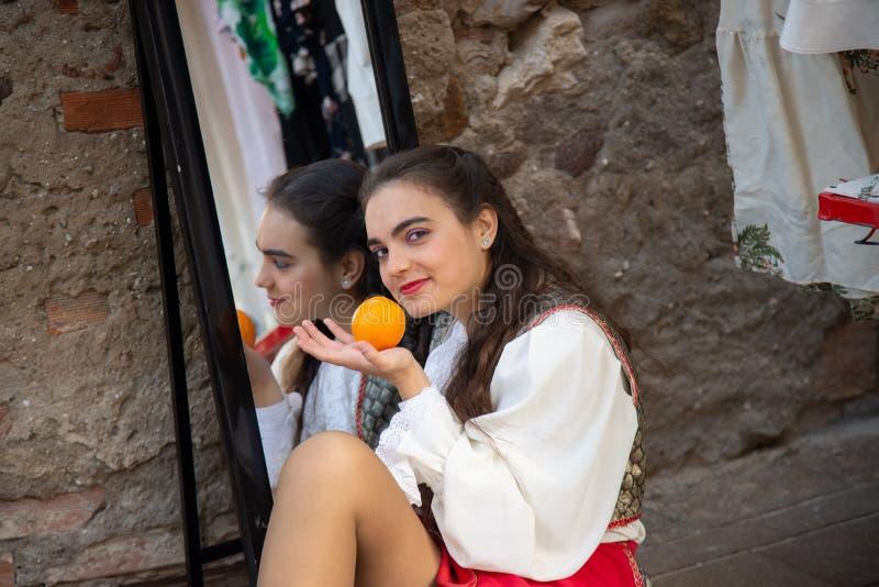 La séance de fille s'est reflétée dans un miroir, tenant une orange dans des ses mains photo libre de droits