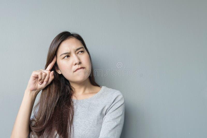 La séance et le regard asiatiques de femme de plan rapproché à l'espace avec le visage de pensée sur le mur brouillé de ciment on photos libres de droits