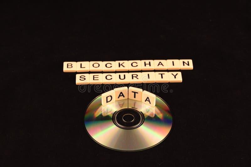 La sécurité de chaîne de bloc a défini dans des tuiles au-dessus d'un CD avec des données se reflétant au milieu sur un fond noir photos libres de droits