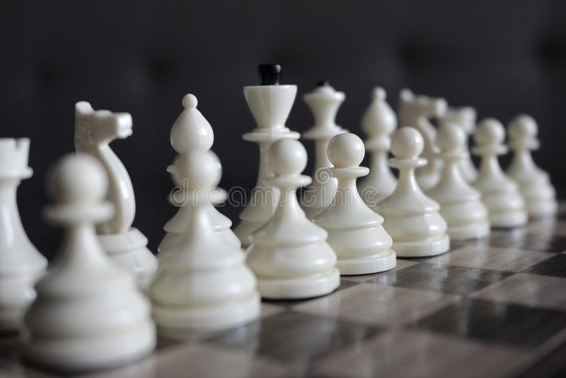 La série d'échecs blancs figure concentré et unfocused sur l'échiquier en bois en tant que concept de jeu de stratégie photos libres de droits