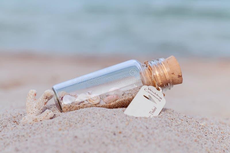 La sabbia e la conchiglia in bottiglia hanno messo sopra la spiaggia immagine stock