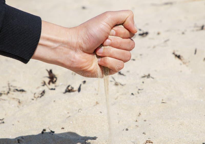 La sabbia versa dalla mano dell'uomo immagine stock