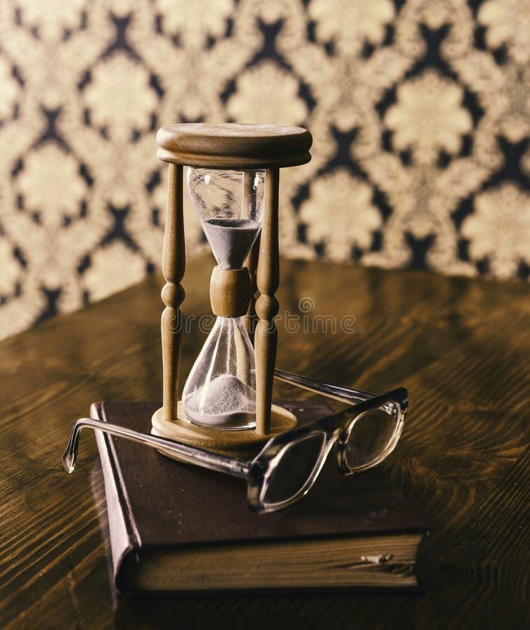 La sabiduría atribuye concepto Reloj de arena, libro viejo y lentes en la tabla de madera, fondo del modelo Arena que cae abajo foto de archivo libre de regalías