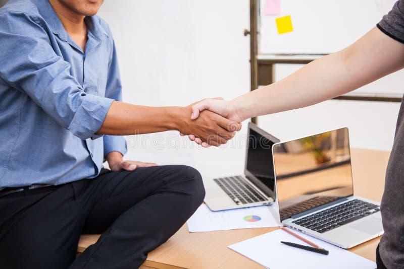 La sacudida de los hombres de negocios entrega la tabla por completo con los dispositivos modernos del ordenador portátil en la r imagen de archivo libre de regalías