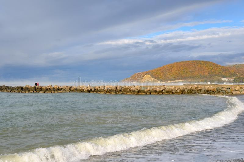 La saison de plage est terminée Deux personnes solitaires marchant le long du brise-lames dans Dzhubga sur le fond du ` de hériss photos stock