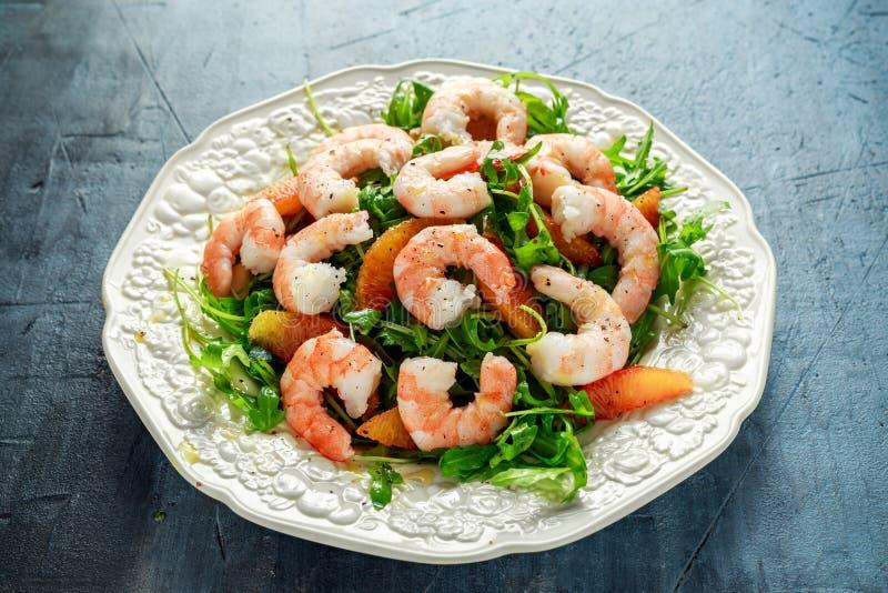 La salade asiatique de crevette de style avec la fusée et l'orange sanguine sauvages a servi avec les cales de citron et la bruin photographie stock libre de droits