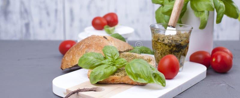 La salade caprese en pain frais et le pesto sauce pour le déjeuner un sandwich à petit déjeuner avec le basilic et le mazarella C images libres de droits