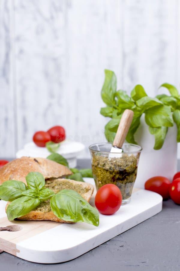 La salade caprese en pain frais et le pesto sauce pour le déjeuner un sandwich à petit déjeuner avec le basilic et le mazarella C photos stock