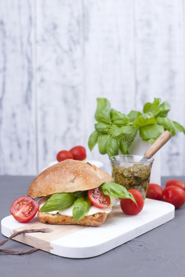 La salade caprese en pain frais et le pesto sauce pour le déjeuner un sandwich à petit déjeuner avec le basilic et le mazarella C images stock