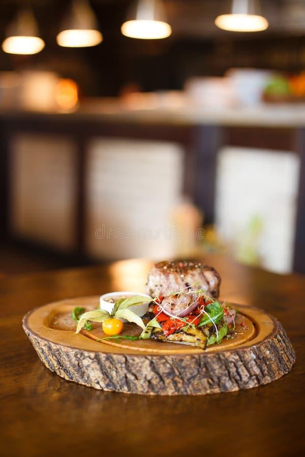 La salade délicieuse aux oignons, piments, bazilik, viande grillée placée près de la tasse de sauce sur le conseil en bois au images libres de droits