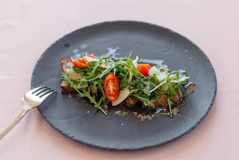 La salade de bifteck de veau avec l'arugula, laitue, divise en deux des tomates-cerises, parmesan images libres de droits
