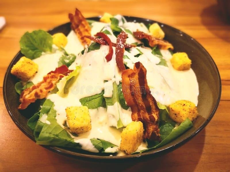 La salade de César dans la cuvette noire, ingrédients tels que le bébé verdissent C photographie stock libre de droits