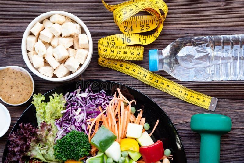 La salade de légume frais et la nourriture saine pour l'équipement de sport pour des femmes suivent un régime le régime avec le r photos stock