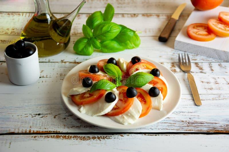 La salade saine d'été faite avec les tomates espagnoles organiques et le mozzarella faible en calories a servi avec le basilic fr images libres de droits