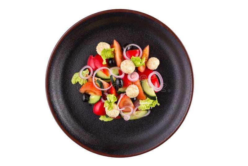 La salade savoureuse avec le calmar, légumes et orange, s'est habillée avec de la sauce d'un plat noir Salade dans un plat d'isol image stock
