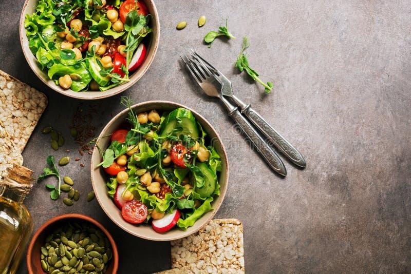 La salade végétale de vegan frais avec des pois chiches, laitue, radis, microgreen, tomate, concombre, graines de citrouille Cuve photo stock