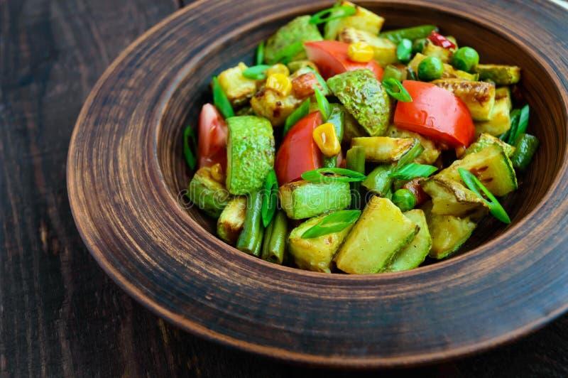 La salade végétarienne diététique avec la courgette grillée, les tomatbackgroundoes frais, le maïs et les herbes dans un argile r photographie stock libre de droits