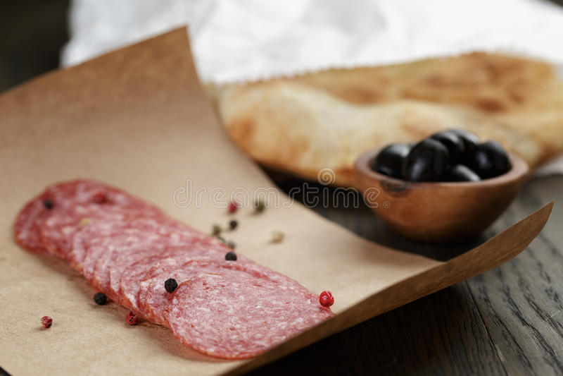 La salchicha secada del salami en de papel alista para el bocadillo fotografía de archivo libre de regalías