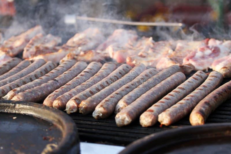 La salchicha y los perritos calientes frescos asaron a la parrilla al aire libre en una parrilla del gas Salchichas en una barbac imágenes de archivo libres de regalías