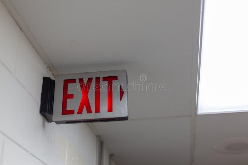 la salida de emergencia roja firma en el cuarto oscuro muestra iluminada de la salida de la oficina imagenes de archivo