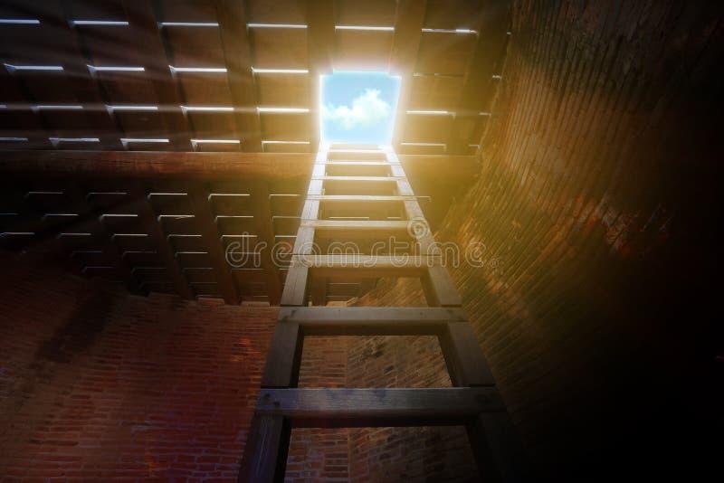 La salida de un cuarto oscuro, la escalera de madera del sótano hasta considera el cielo imágenes de archivo libres de regalías