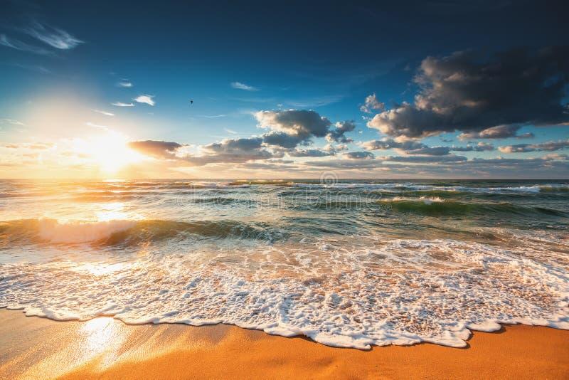 La salida del sol colorida de la playa del océano con el cielo azul y el sol profundos irradia fotos de archivo