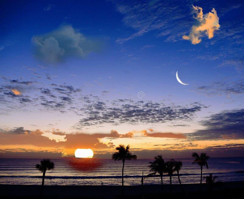 La salida del sol con la luna trae a colores vibrantes al horizonte de la playa cada mañana imagen de archivo