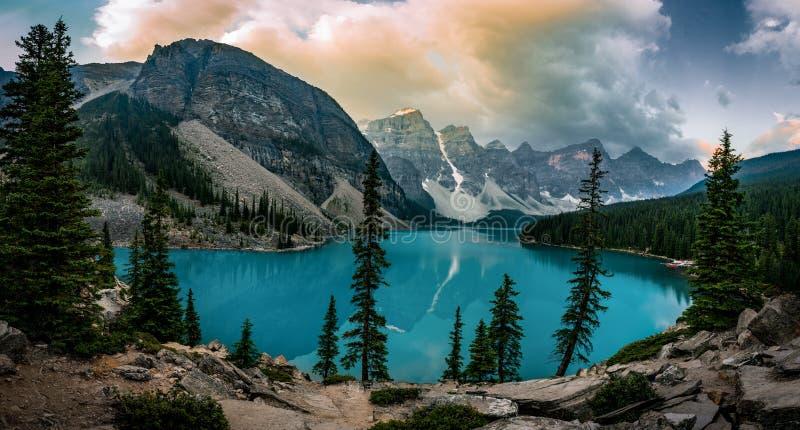 La salida del sol de la opinión del panorama con aguas de la turquesa del lago moraine con pecado encendió las montañas rocosas e foto de archivo