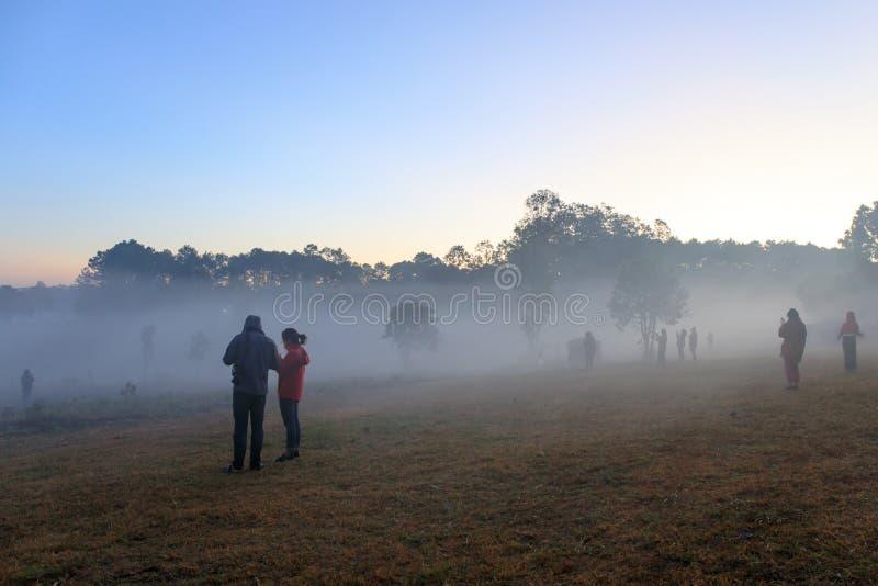 La salida del sol en el parque nacional de Thung Salaeng Luang, la gente o el viajero son tienda de campaña con de niebla o brumo foto de archivo