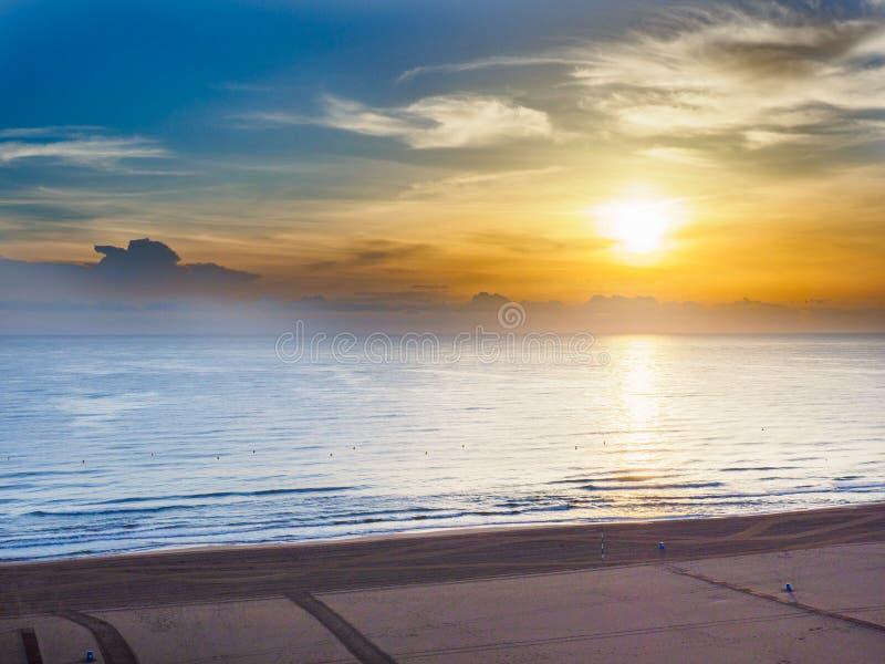 La salida del sol es el sol bajo en el horizonte y reflexiones en el mar en la playa de Gandía, España imágenes de archivo libres de regalías