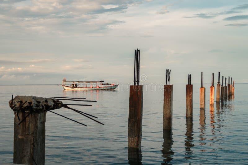 La salida del sol golpea el barco y el embarcadero quebrado - Camboya imagen de archivo