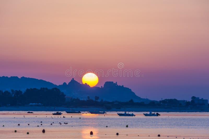 La salida del sol hermosa con el cielo anaranjado, el sol rojo y el oro riegan fotografía de archivo