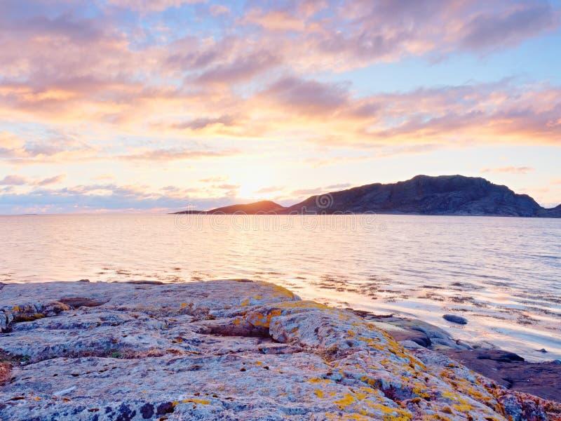La salida del sol hermosa en orilla rocosa y el cielo dramático se nubla fotografía de archivo