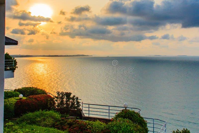 La salida del sol hermosa por la mañana que el sol emite la rotura a través de la nube colorida y refleja la luz ámbar de la sol  imagen de archivo