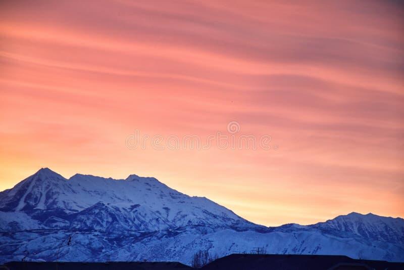 La salida del sol del invierno panorámica, vista de la nieve capsuló Wasatch Front Rocky Mountains, valle de Great Salt Lake y Cl imagenes de archivo