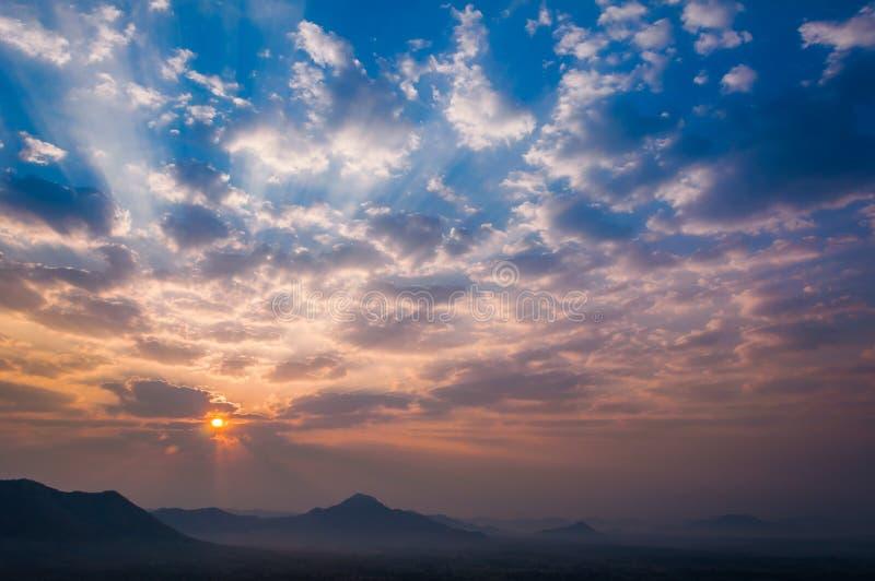 La salida del sol irradia en la nube anaranjada azul del cielo de la mañana con la luz suave del paisaje de la montaña imagenes de archivo