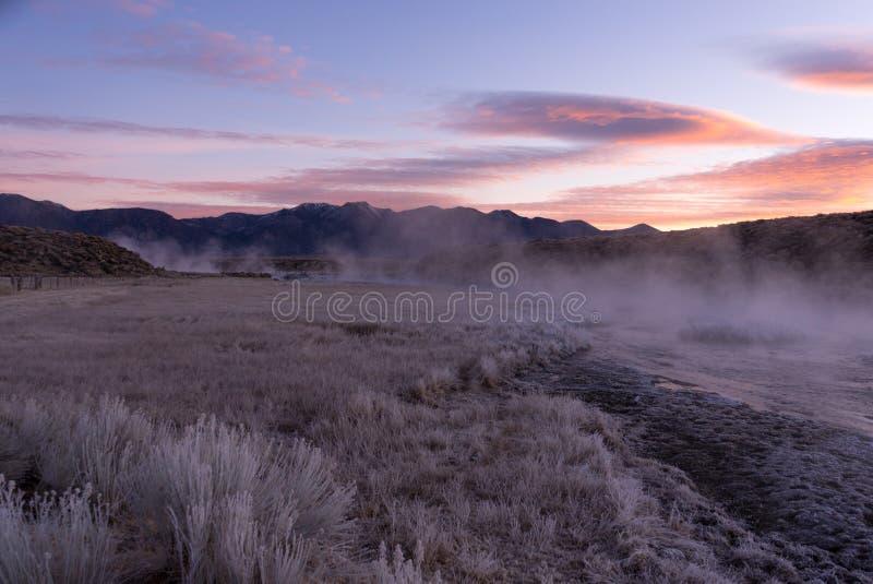 La salida del sol pinta los colores en colores pastel del cielo de Sierra mientras que sube la niebla foto de archivo