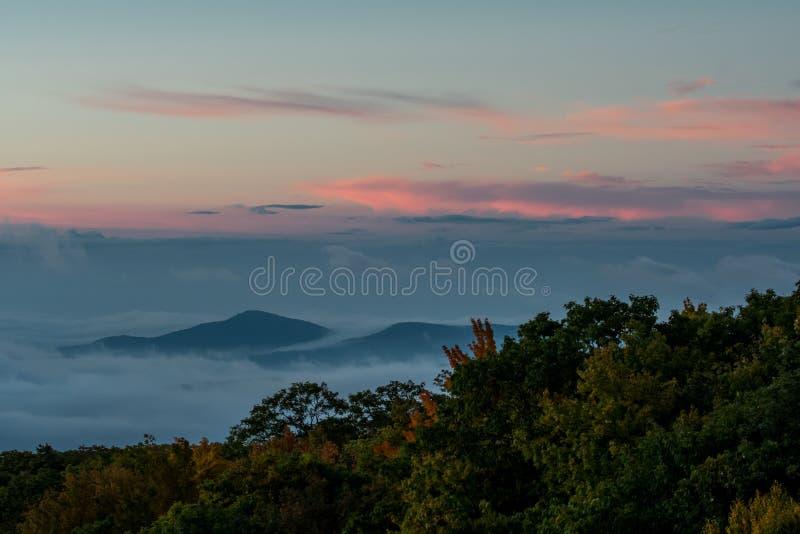 La salida del sol sobre la nube cubrió el valle imagen de archivo