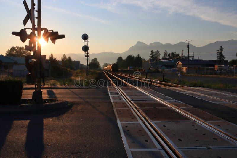 La salida del sol y las vías del tren se encienden reflejado imágenes de archivo libres de regalías