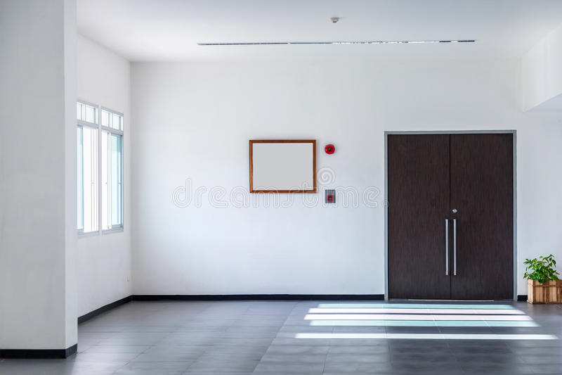 La salle blanche a les portes, les alarmes d'incendie et les arbres bruns dans des pots T photographie stock