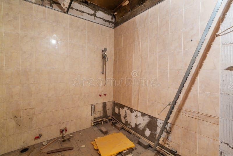 La salle de bains avec la douche avec les murs carrelés, déchets de construction sont en appartement qui est en construction, rem photos stock
