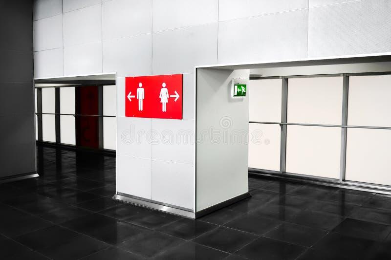 La salle de bains de lieu public entretient le signe d'indication Navigat de toilette photographie stock